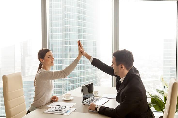 Líder alegre choca la mano con su compañero de trabajo