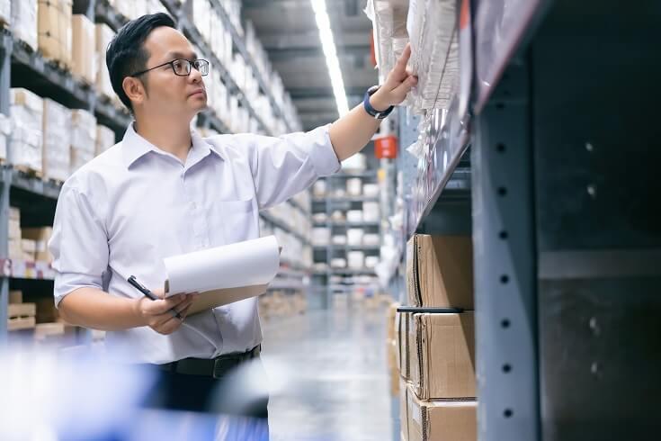 Hombre realiza inventario en la bodega de su empresa