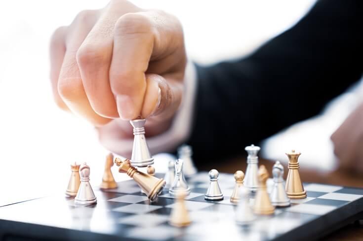 Hombre de negocios sujeta piezas de ajedrez. Analiza la jugada.