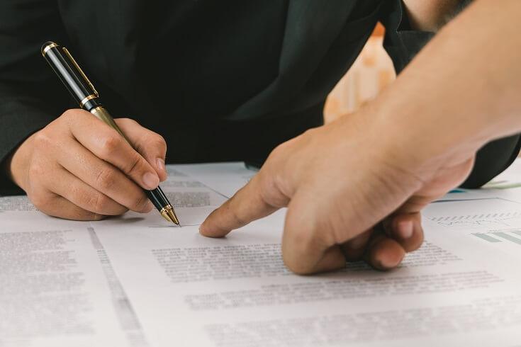 Persona firmando documento de la compañía