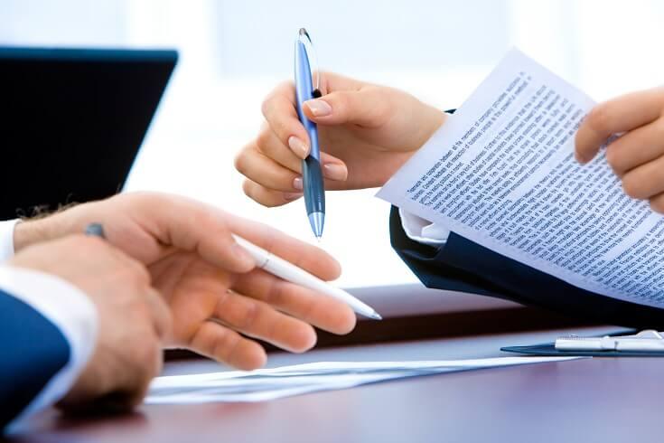 Personal sosteniendo el reglamento y señalando apartados del mismo