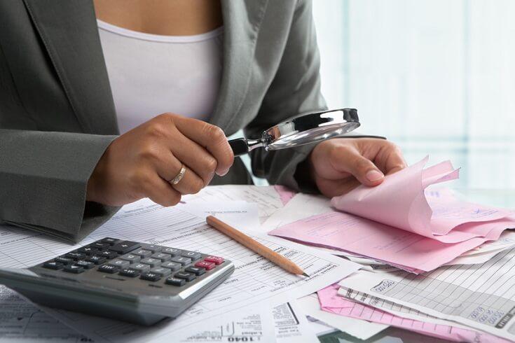Empresario observando detalladamente documentos a través de una lupa