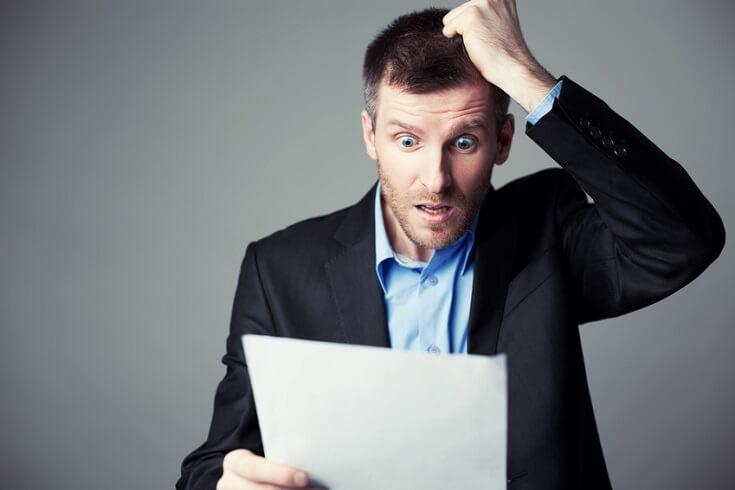 Hombre sorprendido revisando documento